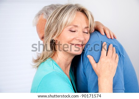 Wife embracing her husband with eyes closed - stock photo