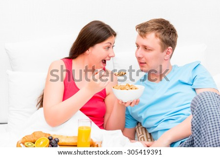 wife feeding her husband breakfast in bed - stock photo