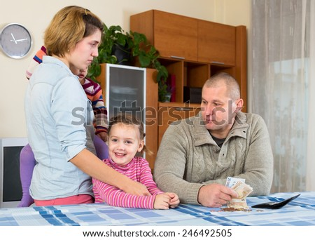 Wife, husband and two their children having a quarell about money at the table at home indoors - stock photo