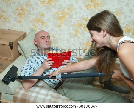 wife is cleaning up whan her husband reading a book over sofa