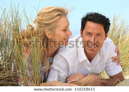 Wife looking at husband on the sand. - stock photo