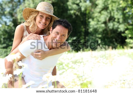 Wife on husband's back - stock photo