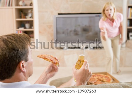 Wife Telling Husband Off For Drinking Beer And Eating Pizza - stock photo