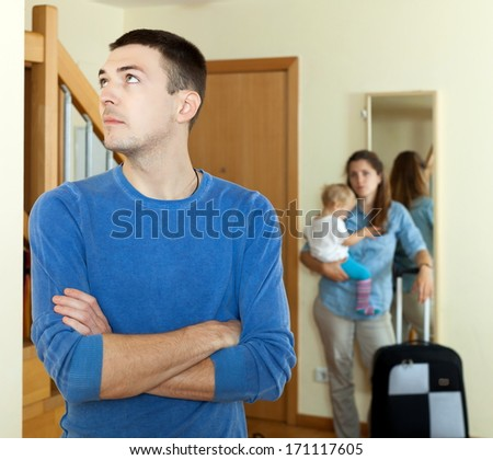 wife with baby girl and suitcase leaving from home - stock photo