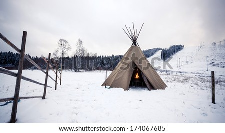 Wigwam with fire in winter forest, Central Finland - stock photo