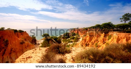Wild angle panoramic landscape with orange cliffs and pines on the Atlantic coastline (Algarve,Portugal) - stock photo
