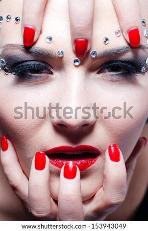Wild animal or vampire looking woman with bright red lips and manicure