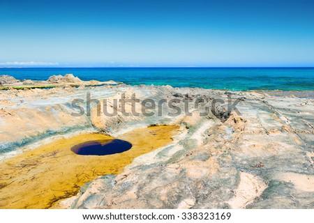 Wild beach with turquoise water and volcanic stones. Crete island, Greece.  - stock photo