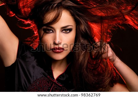 wild beauty with long flying hair and red back light, studio dark - stock photo
