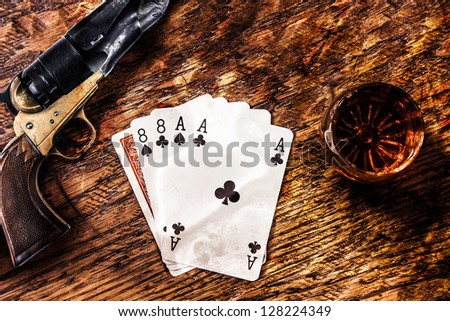 Wild Bill Dead Mans Hand with a whiskey shot and a colt revolver - stock photo