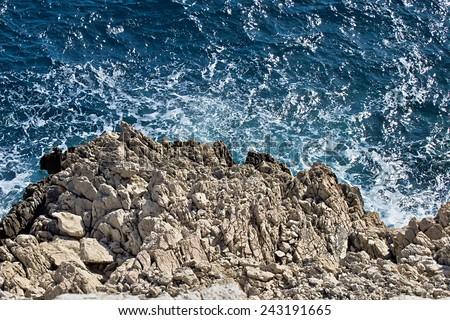 wild blue sea hitting rocky coast and foaming - stock photo