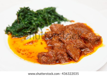 Wild boar stew with hot sauce and spinach, close-up - stock photo