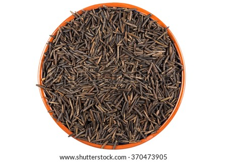 Wild brown rice in bowl and loose over white background