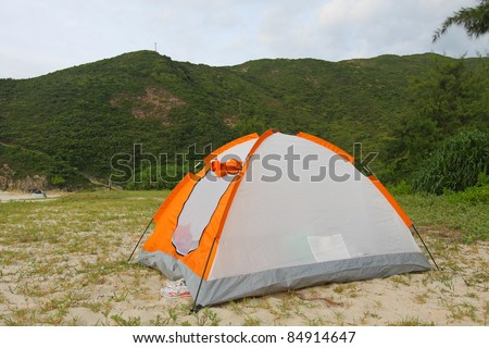 Wild camping on beach with tent - stock photo