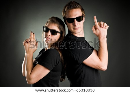 wild couple with sunglasses and finger guns - stock photo