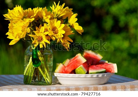 Wild daisies and watermelon on picnic table - stock photo