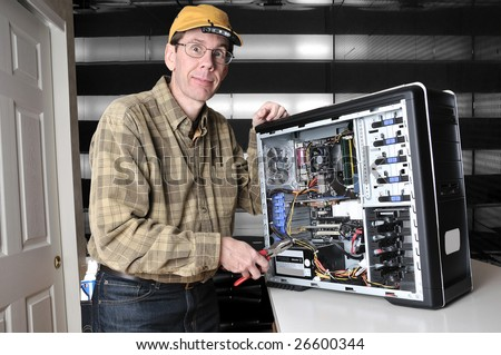 Wild eyed computer geek working on the inside of a PC computer with a screw driver. - stock photo