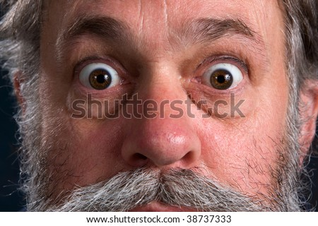 Wild eyed man with his eyes popped open. - stock photo