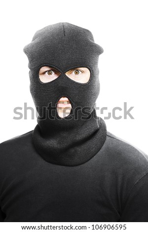 Wild eyed masked bandit concealed under a black textile mask looking in desperation at the camera as he realises that he has been caught in the act - stock photo