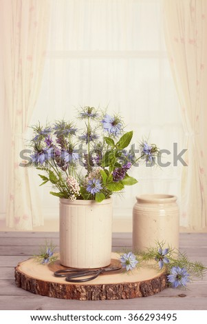 Wild flower arrangement with scissors against a brightly lit window - stock photo
