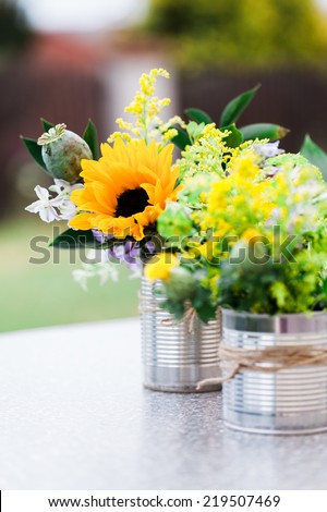 Wild flowers in cane vase on a garden table - stock photo