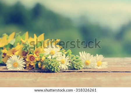 Wild flowers on old wooden table against the background of the landscape. The background for the text. Tone correction in retro style. - stock photo
