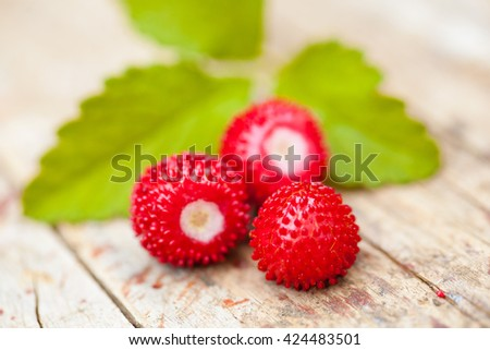 Wild forest strawberries with leaf on wooden desk - stock photo