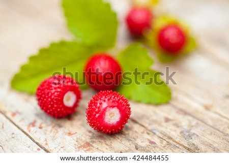 Wild forest strawberries with leaf on wooden desk