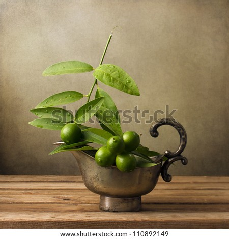 Wild lemons in vintage bowl on wooden table - stock photo