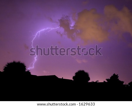 Wild lightning strike with street light reflection on clouds - stock photo