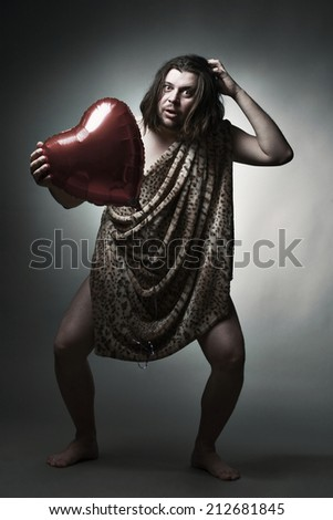 Wild man in leopard skin hold big red heart.  - stock photo