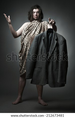 Wild man in leopard skin hold nice jacket to try.  - stock photo