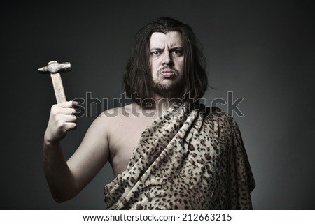 Wild man wearing leopard skin hold old hammer. - stock photo
