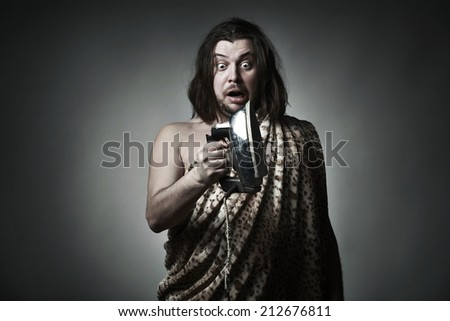 Wild man  wearing leopard skin hold old iron. - stock photo