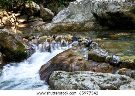 wild mountain river with small waterfalls running trough the forest - stock photo