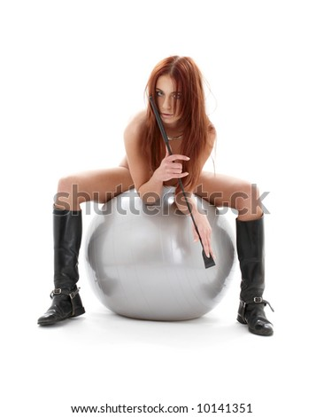 wild redhead in boots with crop on silver ball - stock photo