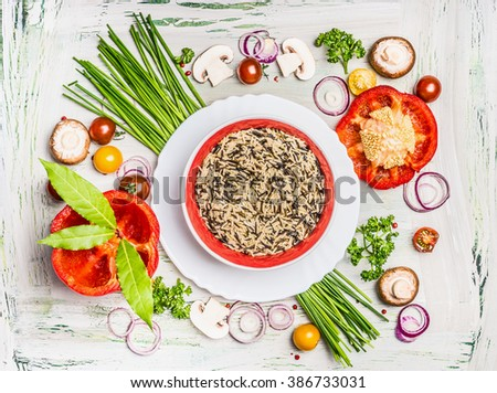 Wild rice dish and various vegetables and seasoning ingredients for tasty vegetarian cooking on light  rustic wooden background, top view composing. Healthy eating and diet food concept.  - stock photo