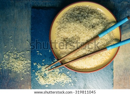 wild rice in ceramic bowl on wooden background - stock photo
