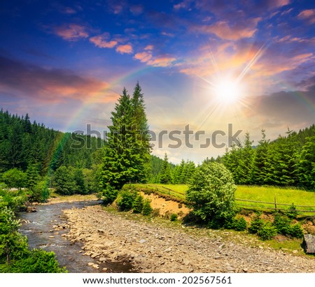 wild river flowing between green mountain forests at sunset with rainbow - stock photo