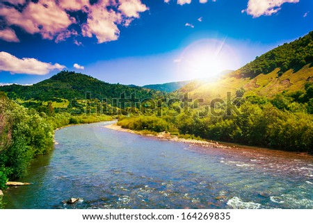 wild river flowing between green mountains on a clear summer day - stock photo