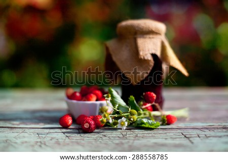 wild strawberry jam on wooden table, soft red and green bokeh background  - stock photo