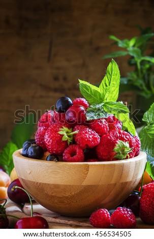 Wild summer berries in bowl, dark background, selective focus - stock photo