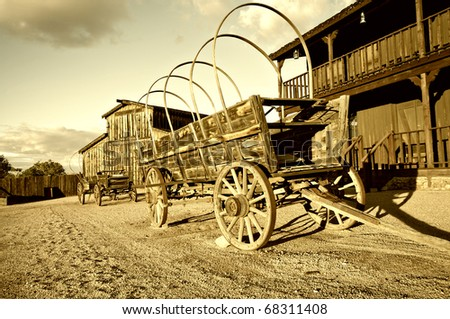 Wild west Cowboy town with wagon in foreground. - stock photo