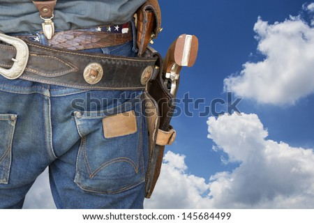 wild west cowboy with gun and leather holster on blue sky