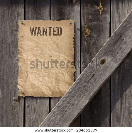 Wild West style wanted poster on weathered plank wood door - stock photo