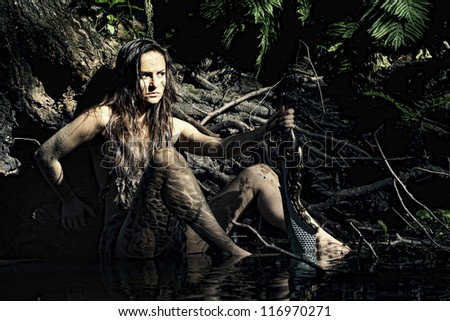 Wild woman posing with a loincloth on the nature - stock photo