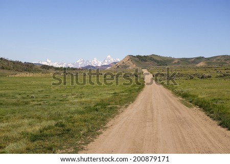 wilderness road with view of Tetons - stock photo