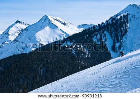 Wilderness Snow Skier: a mature woman skiing un-tracked powder slope in colorado with majestic mountain background near Aspen, CO. - stock photo
