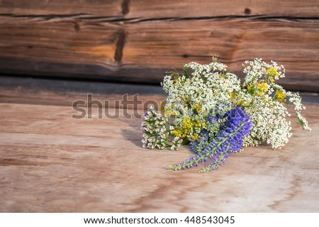 Wildflowers bouquet on old dirty wooden table at sunset. Evening calm scene. - stock photo