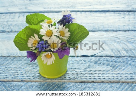 Wildflowers in bucket over blue wood background